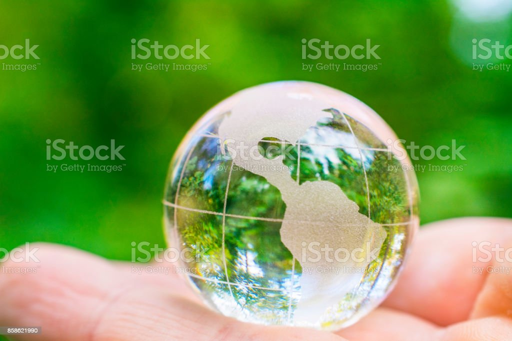 Glass world globe in a palm. Photo is taken in a forest.
