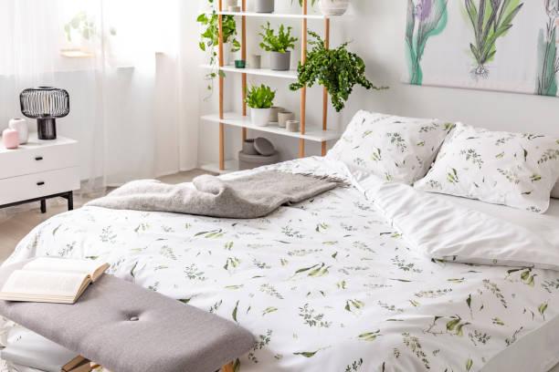 grünpflanze muster auf weiße bettwäsche und kissen auf einem bett in einem schlafzimmer innenraum zu lieben. echtes foto. - gepolsterte bank stock-fotos und bilder