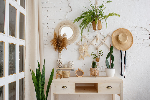 Green plants, dried flowers and cactuses on a table in rustic style. Cozy loft interior with white brick wall