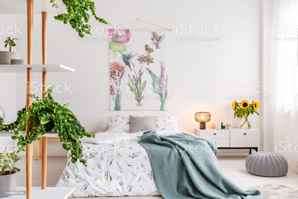 Green Plants On Shelves Beside A Bed Dressed In White Cotton Bedding And  Teal Blue Blanket In A Bright Bedroom Interior Flowers And Birds Painted On  ...