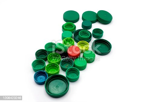 Green plastic bottle caps isolated on white background. PP and PET pollution. Recycling solutions for plastic waste.