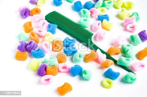 istock Green plastic comb and bright multi-colored scrunchies on white 1158578845
