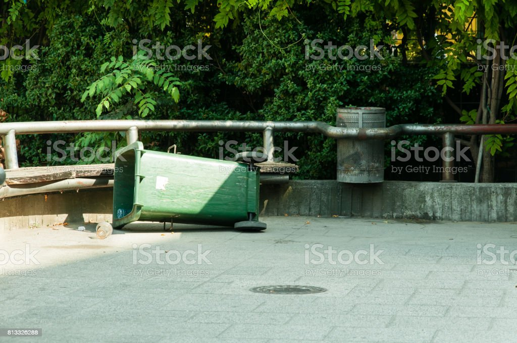 Green plastic garbage can lying on the street. Vandalism concept. stock photo