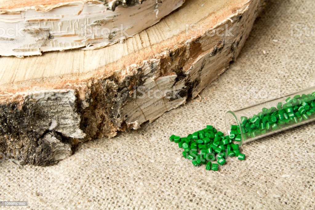 Green Plastic granules on the background birch.The concept of environmental friendliness of Polyethylene, polypropylene material. BPA FREE stock photo