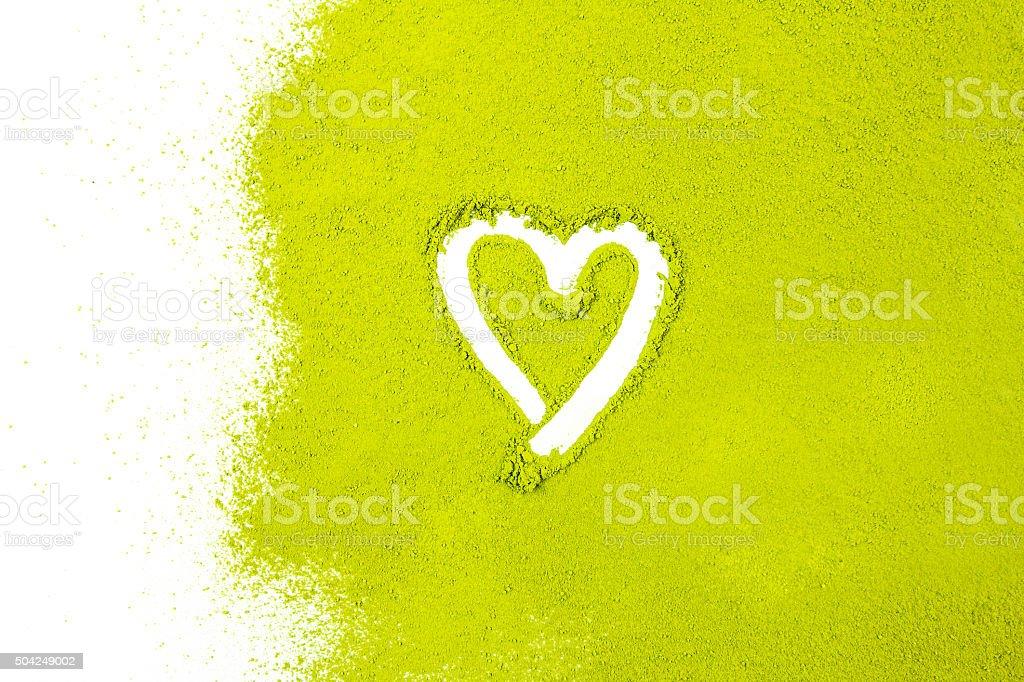 green powder forming heart shape surface close up stock photo