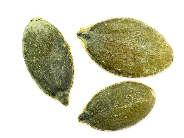 Green pumpkin seeds isolated on a white background stock photo
