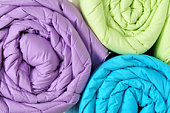 Green, purple, and blue duvet covers rolled up