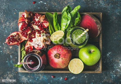 istock Green, purple fresh juices with fruit, greens, vegetables in tray 627779194