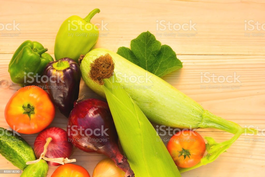 Green, purple peppers, tomatoes, corn, zucchini, blue and yellow onion on a wooden background in diffused light stock photo