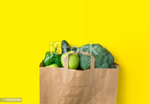 istock Green raw organic vegetables fruits broccoli cucumbers bell peppers apples in brown paper Kraft grocery bag on yellow background. Healthy diet dietary fiber vegan plastic free concept. Poster banner 1150506359