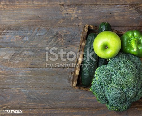 istock Green raw organic vegetables fruits broccoli cucumbers bell peppers apples in box on wooden table. Healthy diet dietary fiber vegan superfoods concept. Poster banner 1173476360