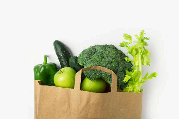 Green raw organic vegetables fruits broccoli cucumbers bell peppers apples celery in brown paper grocery bag on white background Green raw organic vegetables fruits broccoli cucumbers bell peppers apples celery in brown paper grocery bag on white background. Healthy diet online food shopping delivery plastic free concept anti inflammatory stock pictures, royalty-free photos & images
