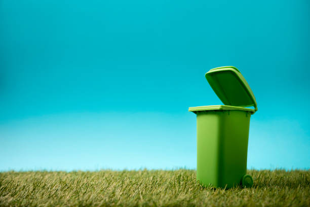 Green recycle bin on green grass and blue sky stock photo