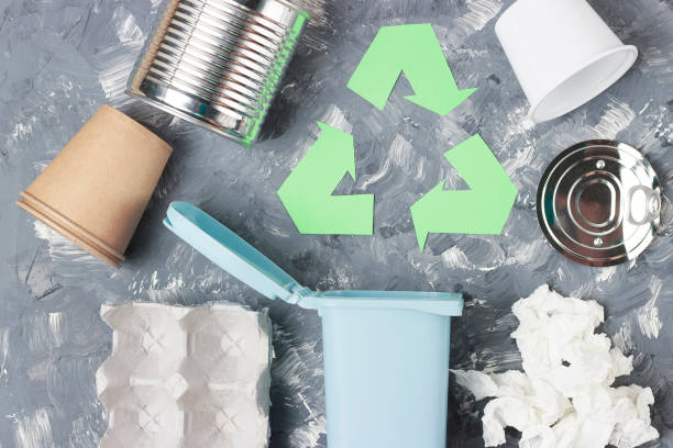 Green recycle garbage symbol and plastic, iron garbage on a gray background, top view. stock photo