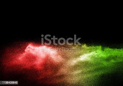 istock Green red color powder explosion cloud  on black background.Green red dust splash on dark background. 1138405845