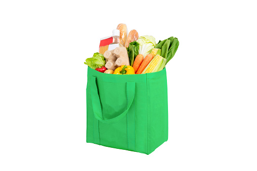 Green reusable shopping bag full of vegetables and groceries isolated on white background
