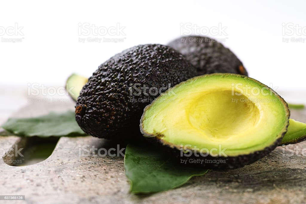 Green ripe avocado with leaves close up 스톡 사진