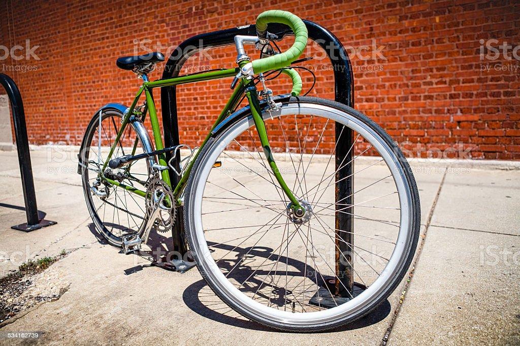 Green Road Bicycle U-Locked To Bike Rack stock photo