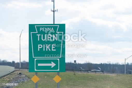 Upper Allen Township, USA - April 8, 2018: Green road sign to Penna Pennsylvania Turnpike highway toll freeway with blue sky outside