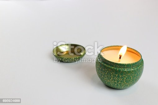 istock Green round candle with flame and cap laying to side 695924688