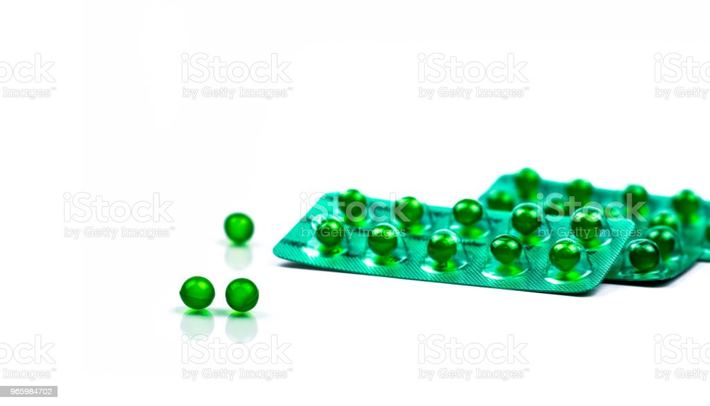 Green round soft capsule pills isolated on white background with copy space. Ayurvedic medicine for indigestion, gas and acidity. Herbal medicine made from Mentha oil and spearmint oil from India - Royalty-free Acid Stock Photo