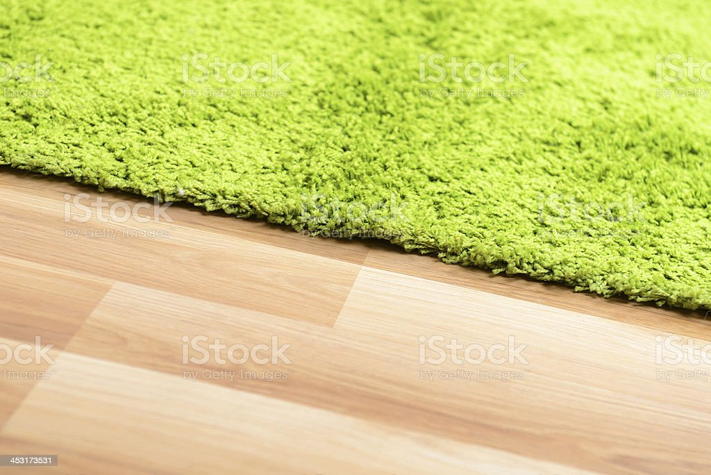 A green rug on top of a wooden floor stock photo
