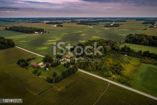 A wide aerial view via drone over the green summer agricultural fields, pastures, and farmsteads in rural Ohio.