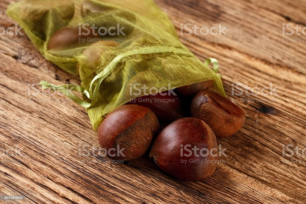 Green sack full of sweet chestnuts stock photo