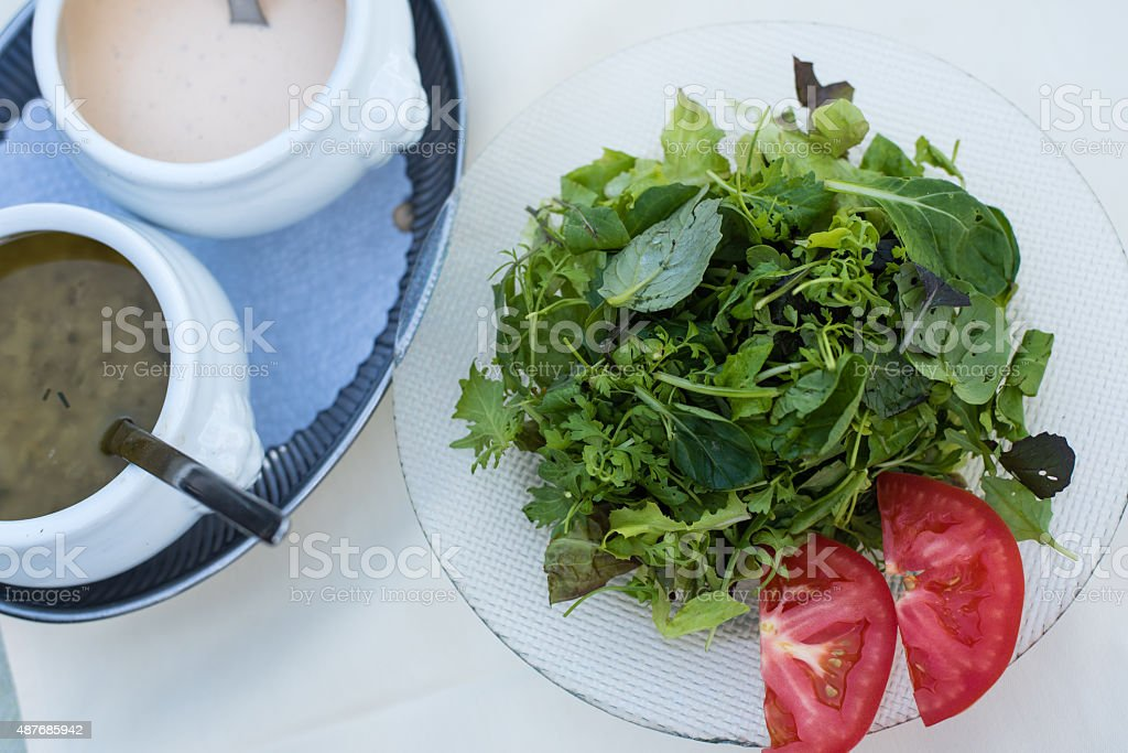 Green Salad and Tomato served with selections of dressings stock photo