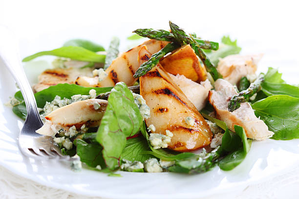 Green salad mix with pears and grilled asparagus with fork stock photo