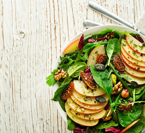 green salad with apple fruit, seeds and nuts - fig salad imagens e fotografias de stock