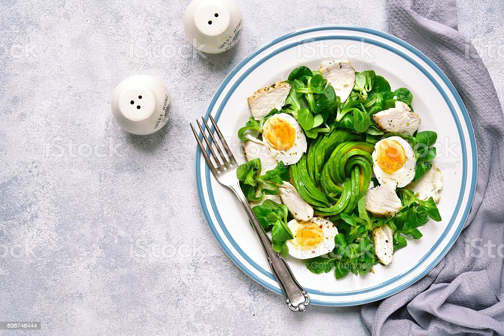Green salad with chicken,avocado and eggs.Top view. stock photo