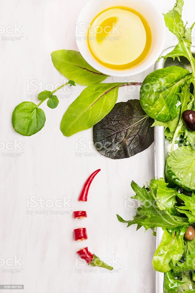 Green salad with dressing on white wooden background stock photo