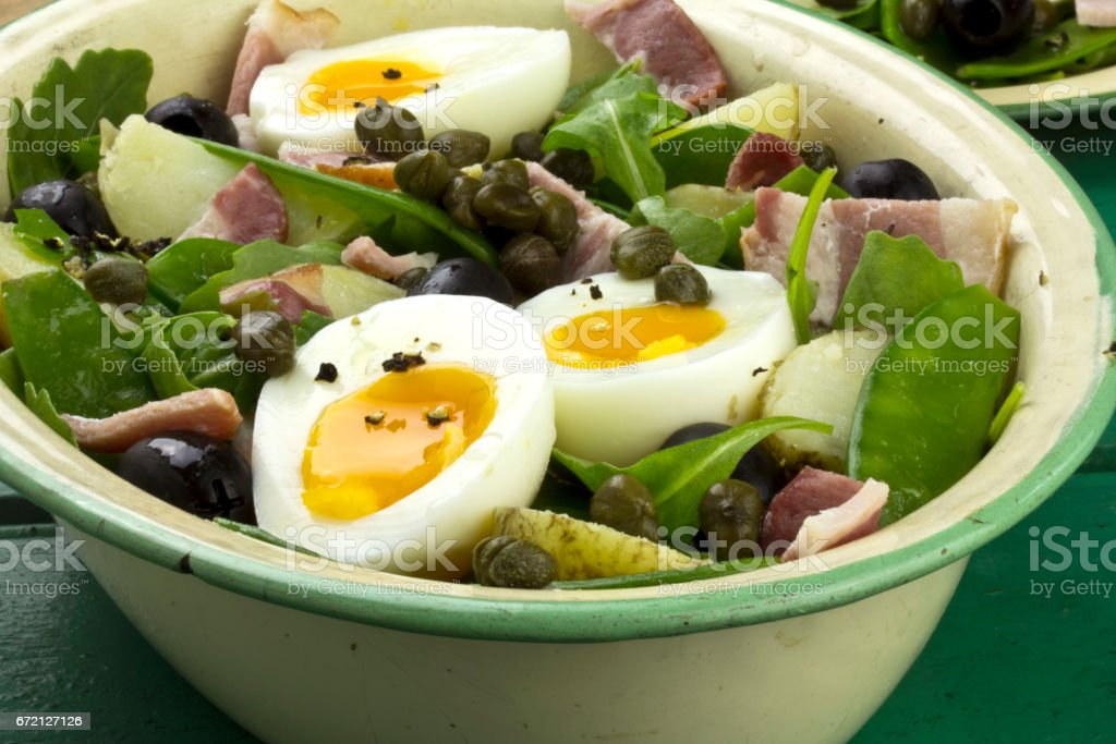 Green salad with potato, bean, bacon, egg and capars stock photo