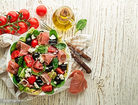 Healthy green salad with prosciutto, olives, tomato and fresh cheese on wooden table background. Healthy meal.