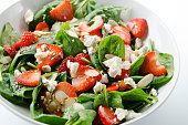 SEVERAL MORE IN THIS SERIES. Fresh salad of baby spinach leaves, sliced strawberries, slivered almonds, feta cheese, and a light dressing. Shallow DOF.