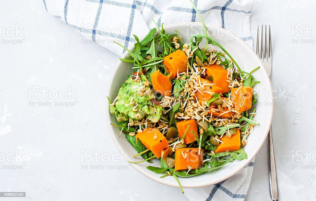 Green salad with sweet potatoes, guacamole and olives. stock photo