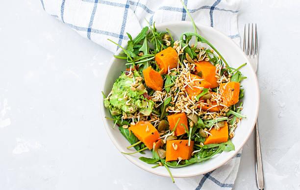 green salad with sweet potatoes, guacamole and olives. - karotten gesund stock-fotos und bilder
