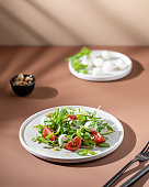 Green salad with tomato in modern style on beige background. Healthy food