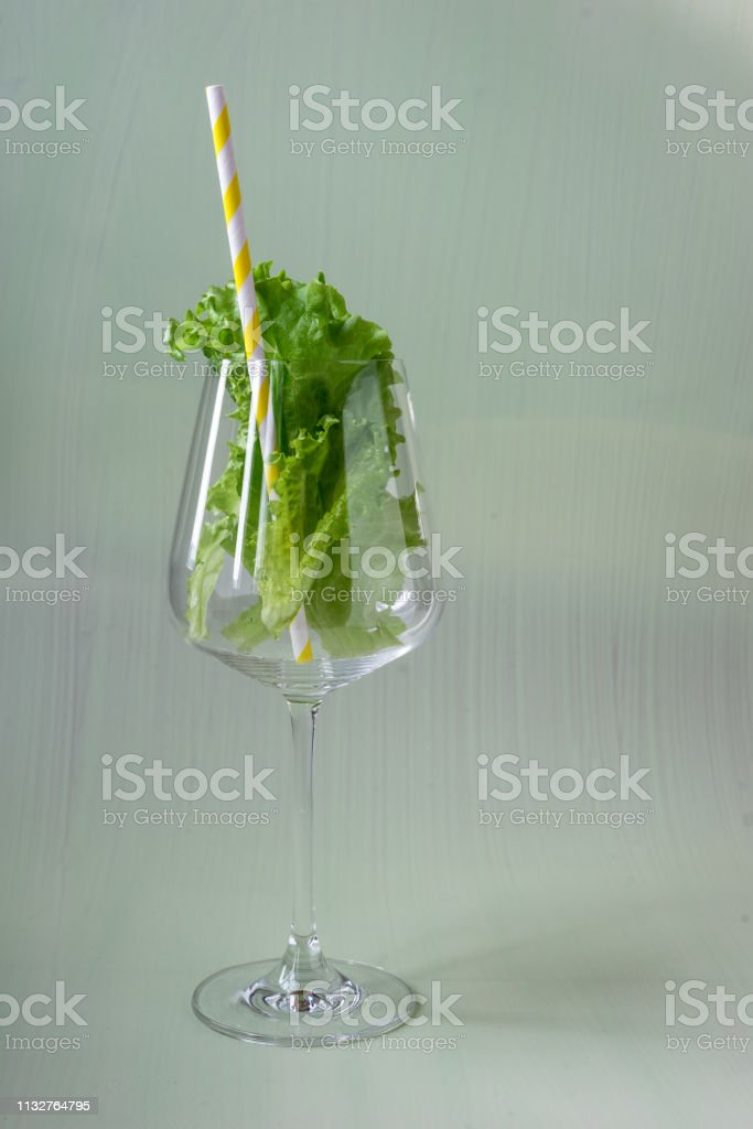 Green salad with yellow and white straw, fresh food and drink...