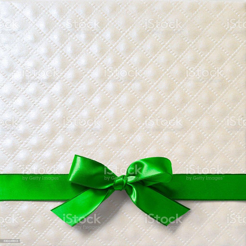 Green satin ribbon on pearl paper stock photo