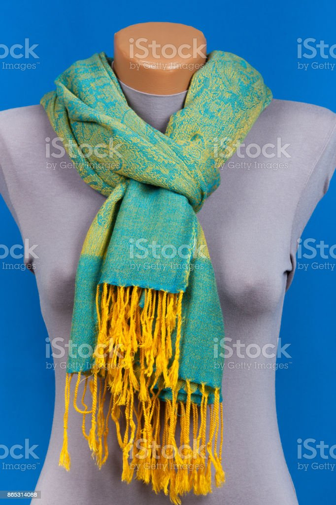 Green scarf on mannequin isolated on blue background. stock photo