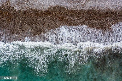 999001484 istock photo Green sea waves hitting the gravel beach of Montenegro 1136781714