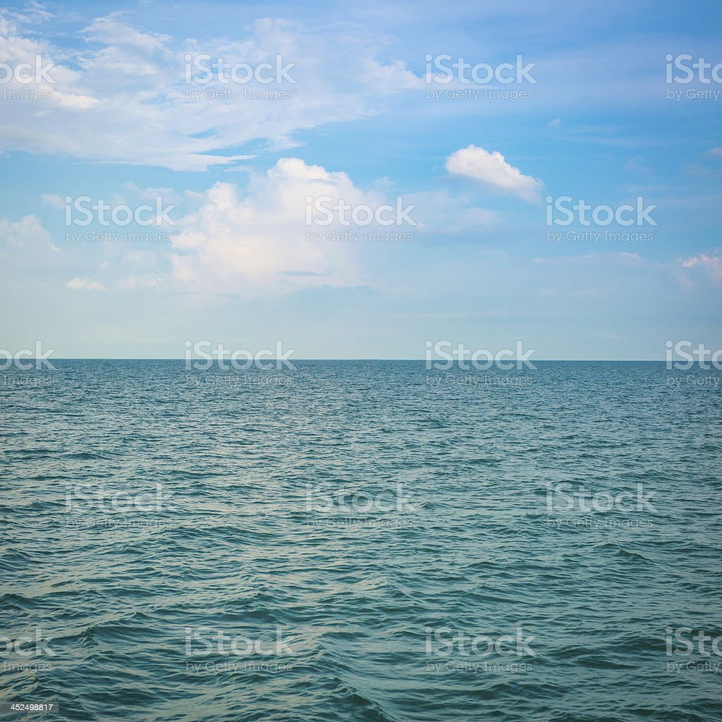 Green sea with waves and clear blue sky stock photo