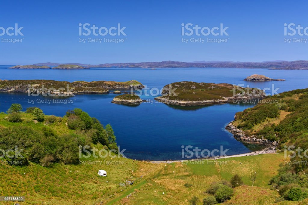 Green seashore with caravan, small rocky islands and mountain range in the distance stock photo