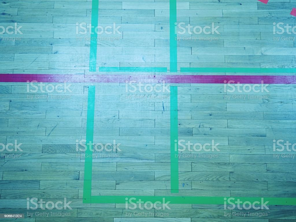 Green shadows of shining floor of sports hall with marking lines and...