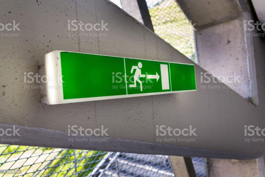 Grün leuchtenden Flucht Ausgangsschild auf weißen Betonwand – Foto