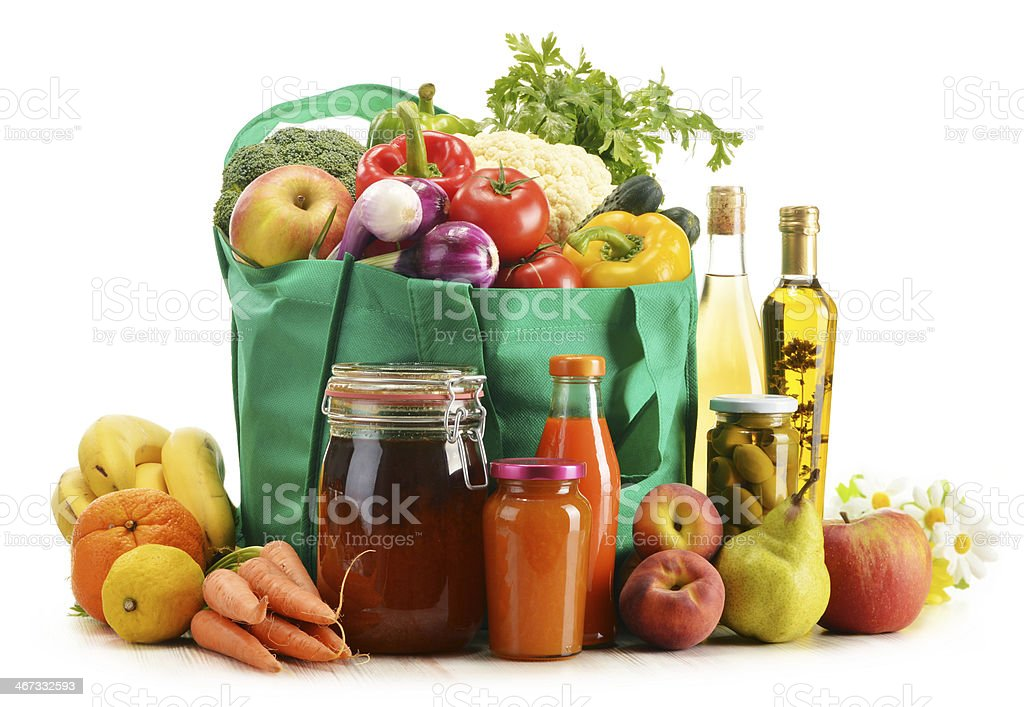 Green shopping bag with assorted vegetables and fruits on white royalty-free stock photo