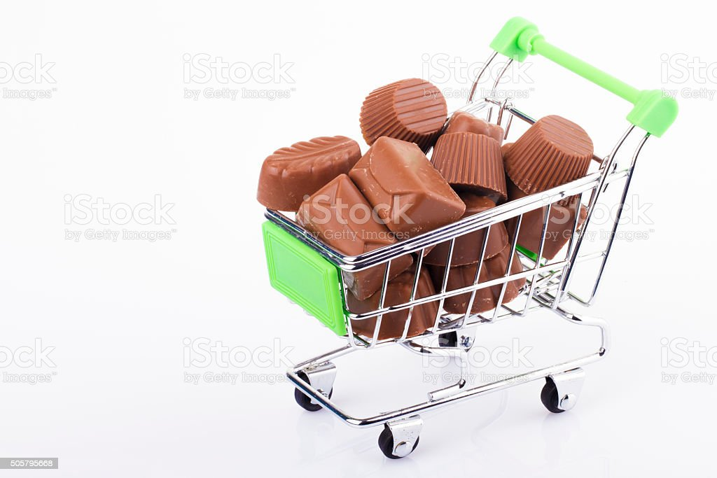green shopping cart with a few chocolate on a white stock photo