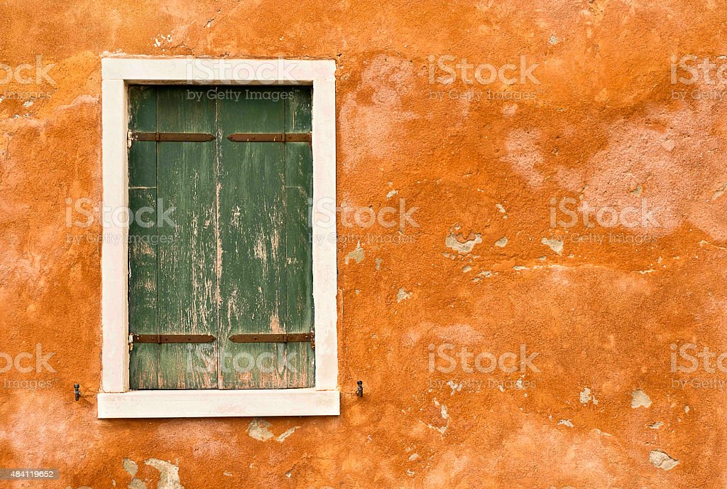 Green shutters on Orange Wall stock photo